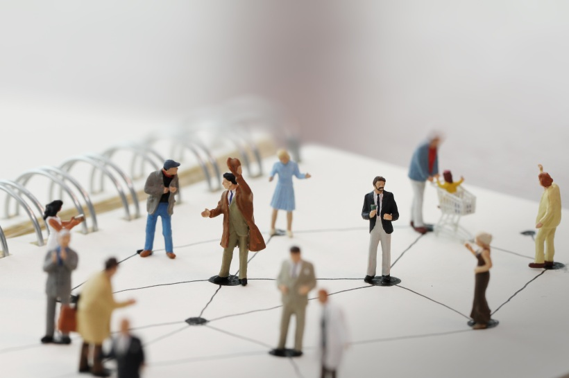 close up of miniature people with social network diagram on open notebook on wooden desk as social media conept